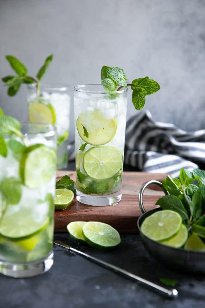 Three classic Mojitos made with white rum, lime juice, sugar, mint, and soda water in a highball glass.