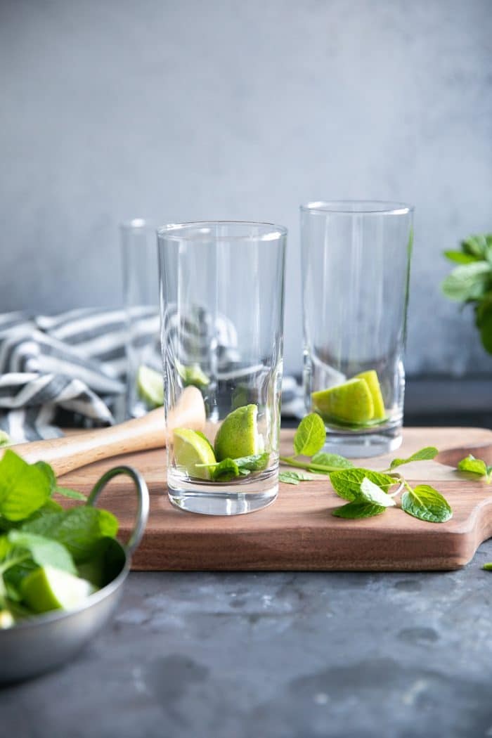 Three highball glasses each filled with two limes and mint leaves.