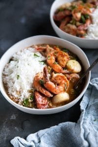 Shrimp, chicken, and sausage gumbo in white bowls and served with white rice.