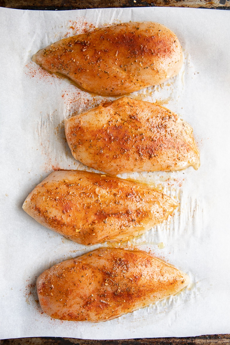 spiced chicken breast lined up on parchment paper
