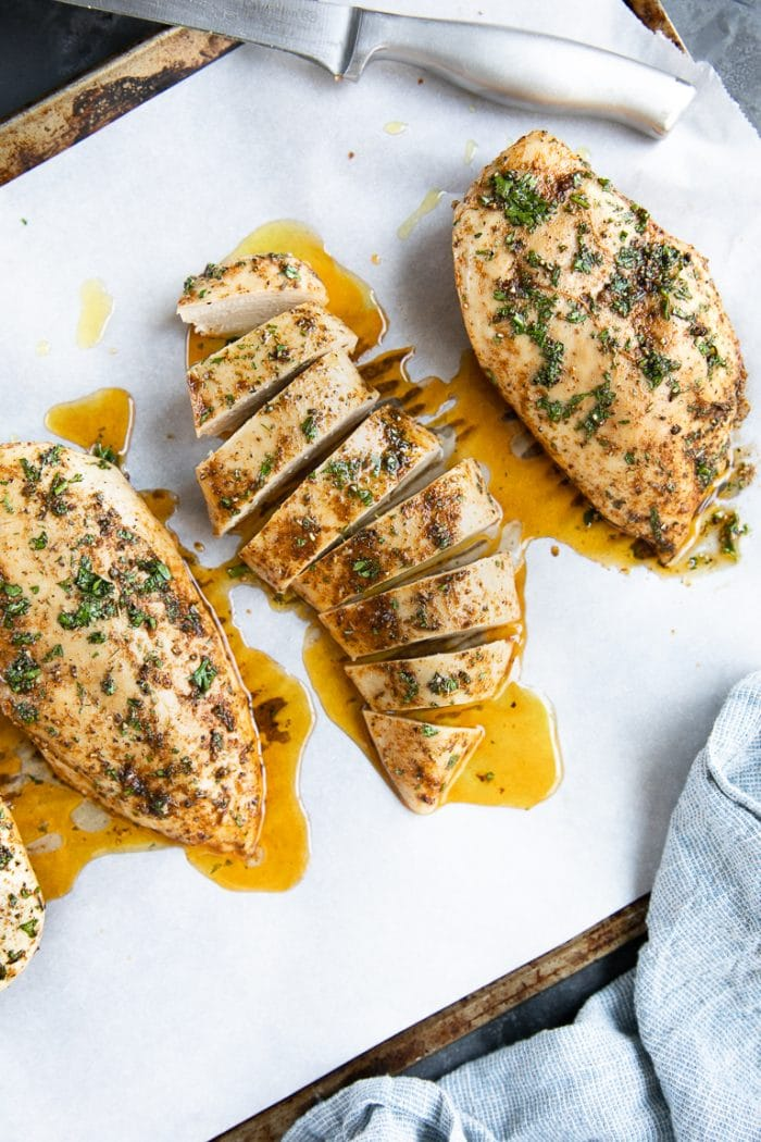 Perfectly baked chicken breasts on a large baking sheet.