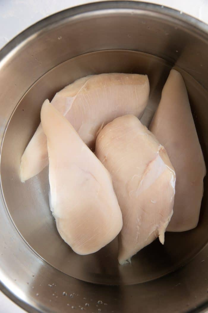 Four chicken breasts brining in a large bowl filled with a mixture of salt and water.