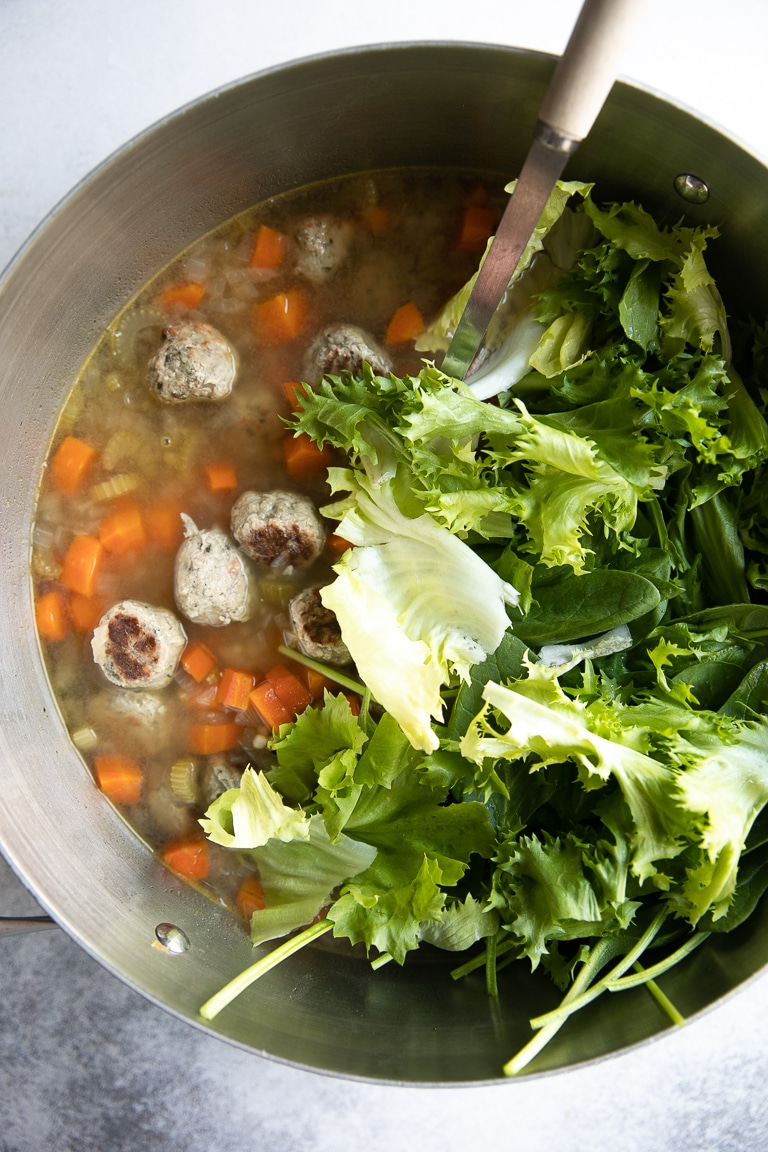 Fresh greens being added to pot of cooking Italian Wedding Soup