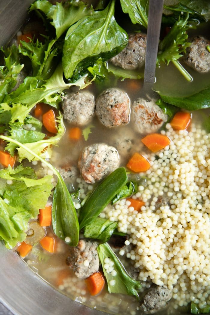 Close up image of a large pot of Italian Wedding Soup filled with mini meatballs, fresh greens, chopped carrots, and mini pasta.