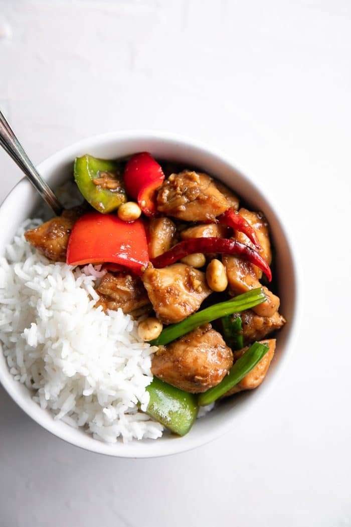 Overhead image of a white bowl filled with white rice and Kung Pao Chicken.