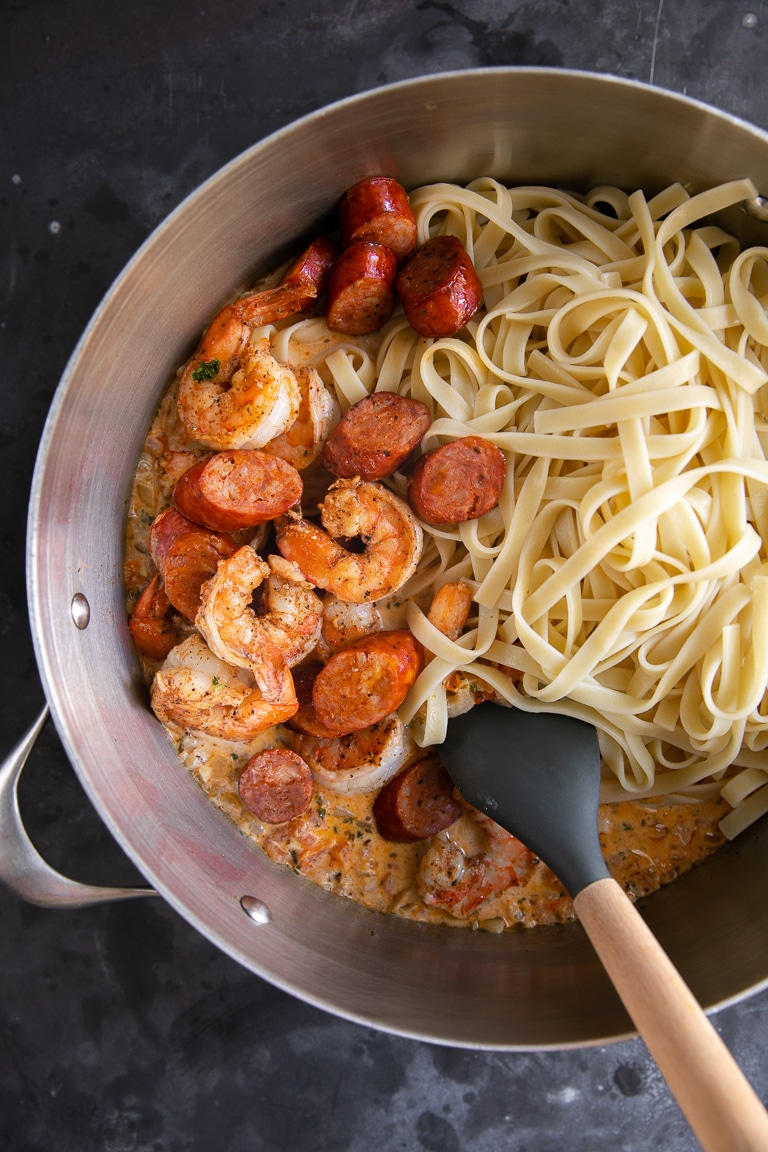 A pot full of shrimp sausage and noodles in sauce