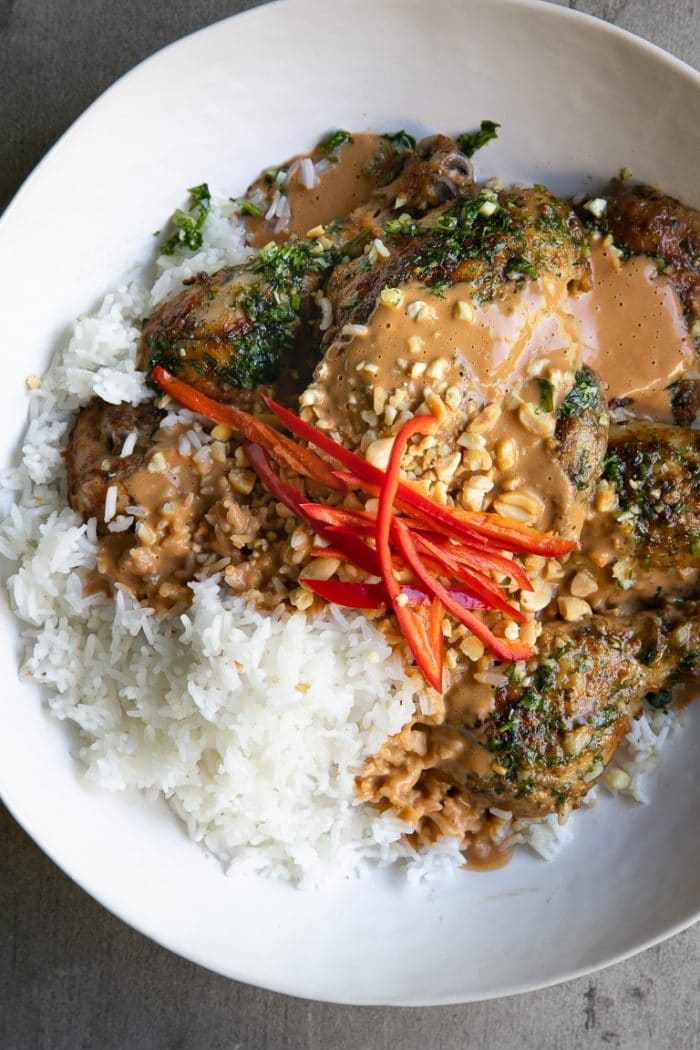 Overhead image of Grilled Thai Chicken smothered in Thai peanut sauce.