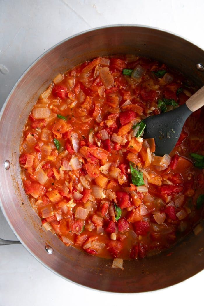 Large pot filled with sauteed tomatoes, onions, garlic, and fresh basil.