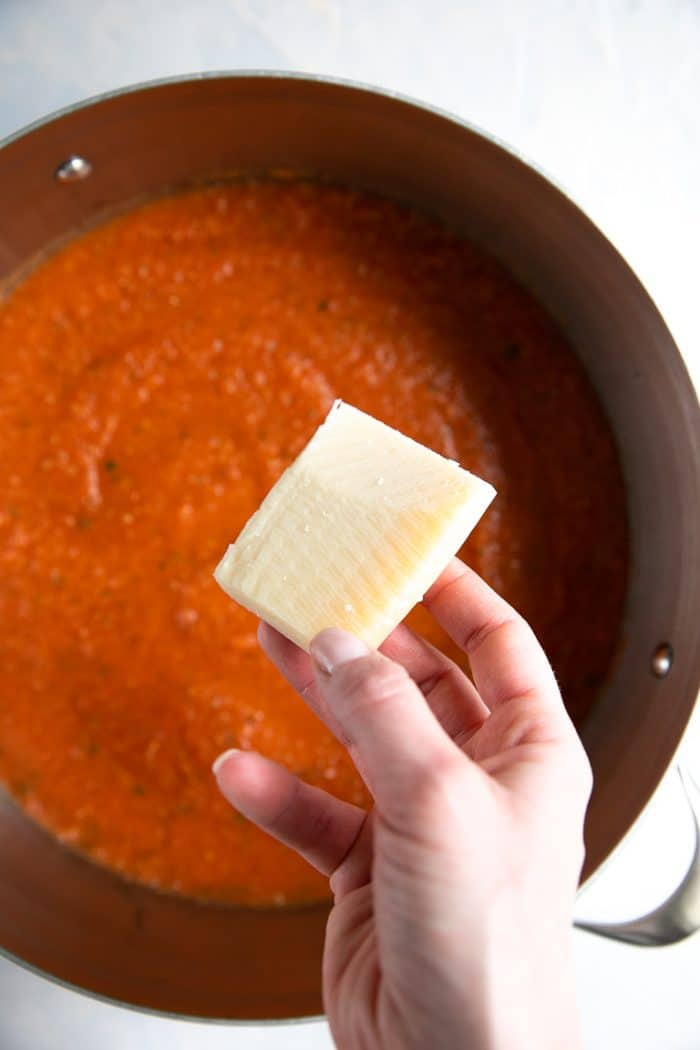 Cheese rind being adding to a large pot filled with marinara.