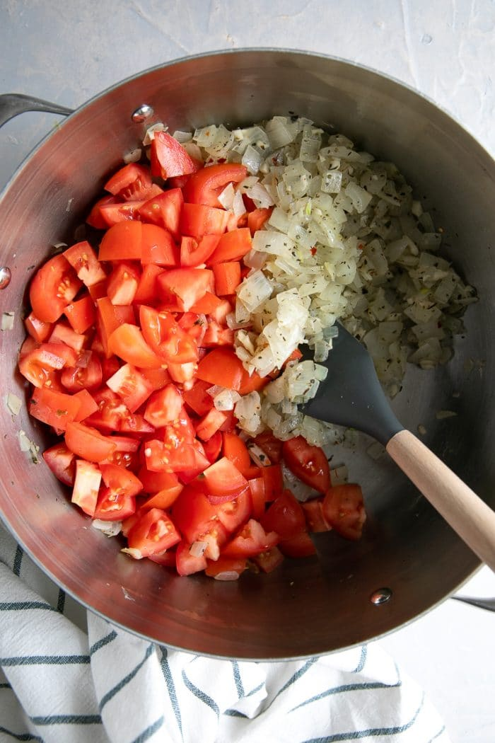 Large pot filled with sauteed onions and chopped Roma tomatoes.