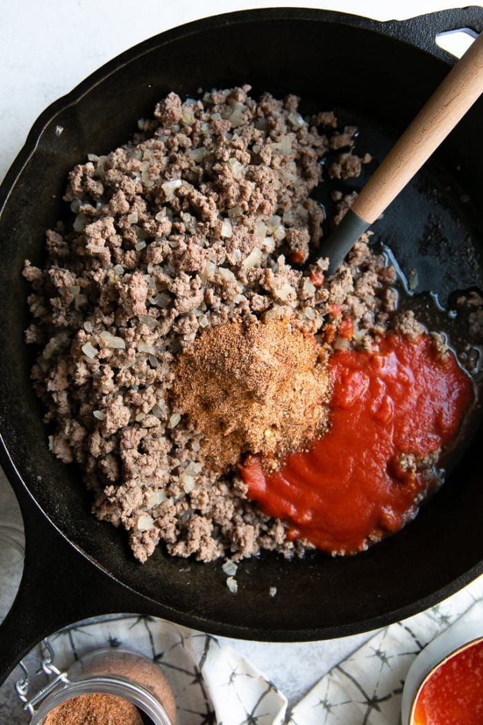 Overhead image of a black cast iron skillet filled with cooked ground beef, taco seasoning, and tomato sauce.
