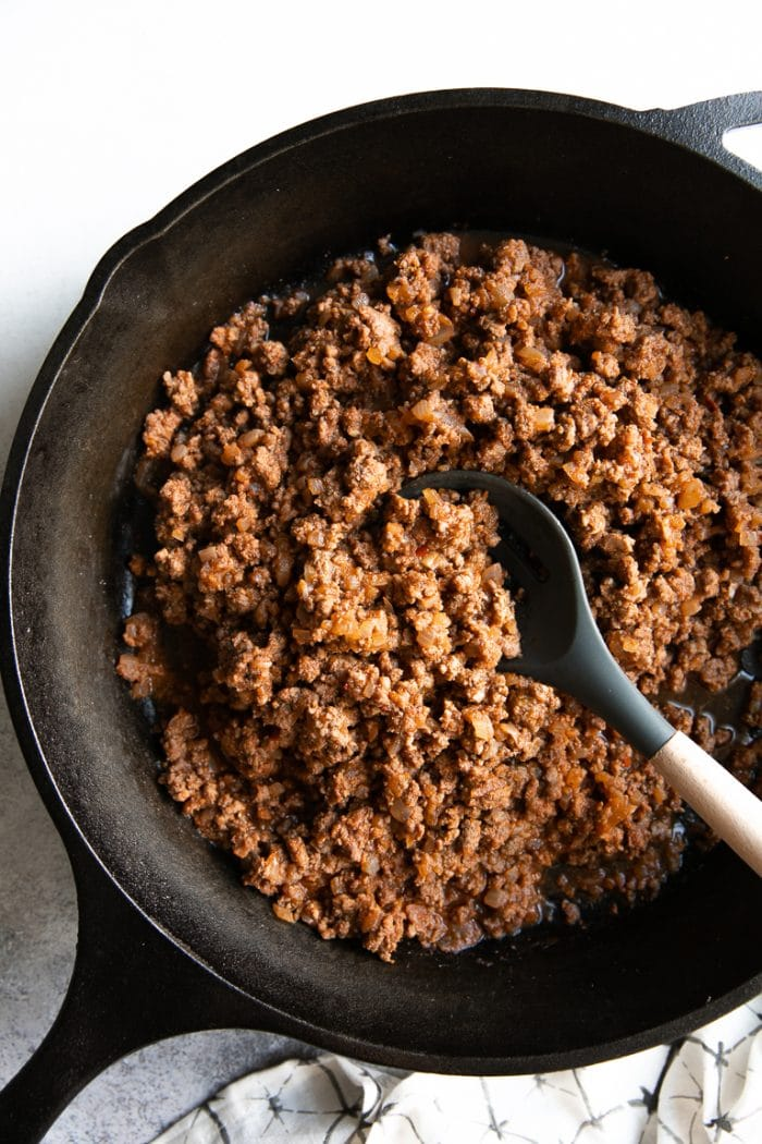 Fully cooked ground beef taco meat in a large black cast iron skillet.