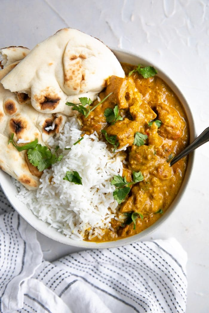 Shallow white bowl filled with creamy butter chicken and rice.