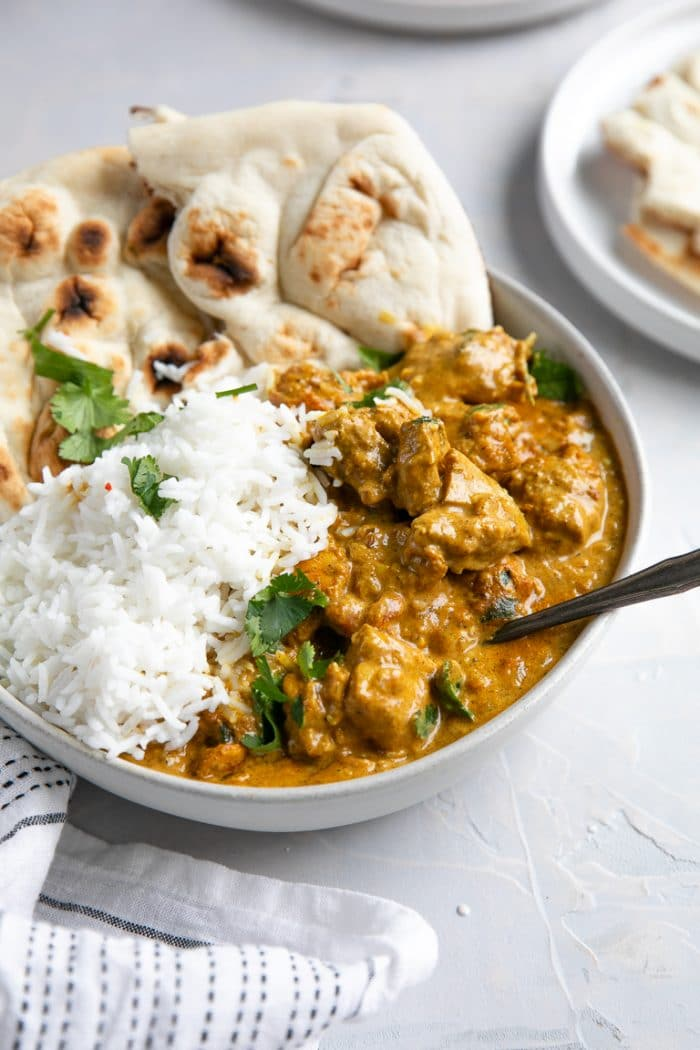 White bowl filled with creamy butter chicken and rice served with naan bread.