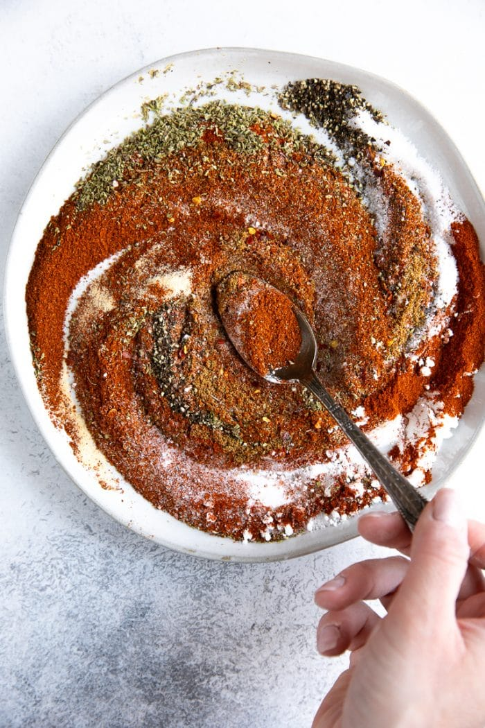 Mixing together the herbs and spices on a white plate to make homemade taco seasoning.