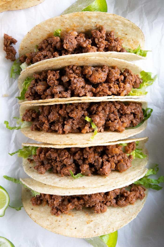 Close-up overhead image of crunchy taco shells filled with ground beef taco meat.