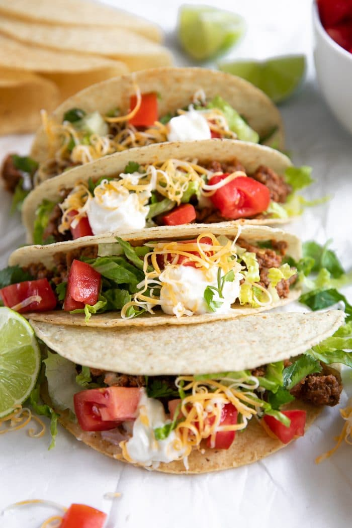 Ground Beef Tacos Recipe with lettuce, tomato, shredded cheese, and sour cream in crunchy taco shells.