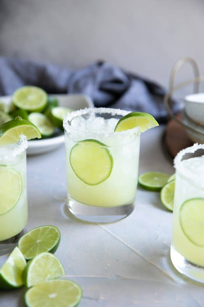 Several glasses filled with classic margarita and garnished with a lime.