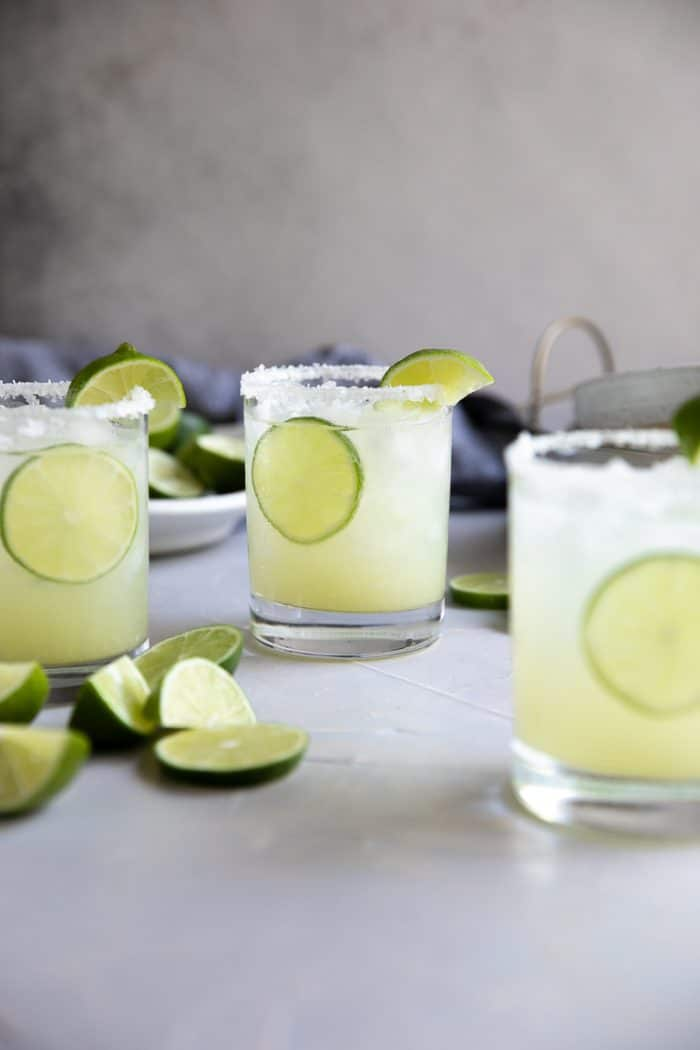 Three glasses filled with classic lime margarita on the rocks.