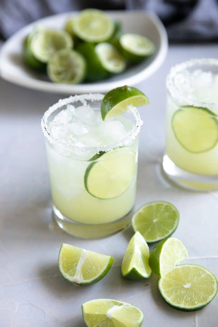 Classic margarita garnished with limes and served with salt.