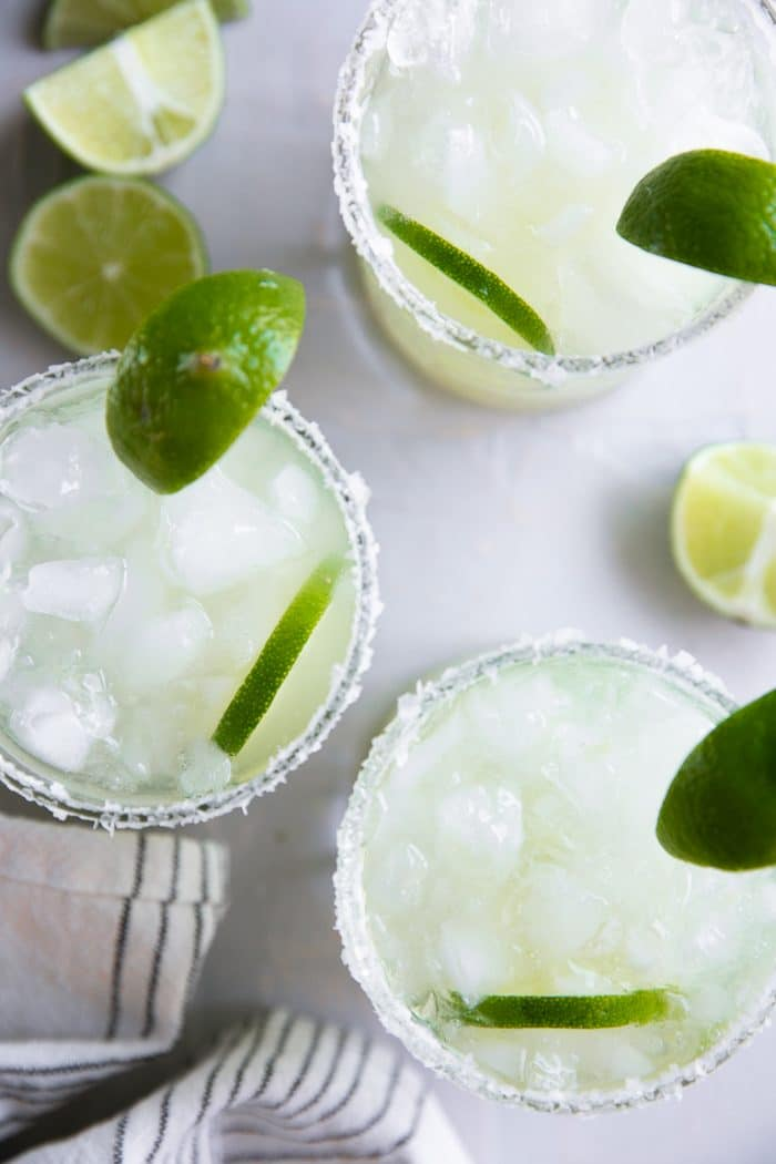 Overhead image of three lime margaritas on the rocks with salt.