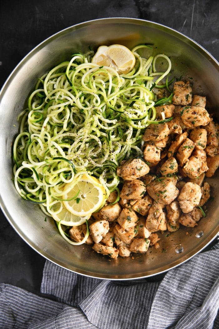 Large skillet filled with cooked chicken bites and zucchini noodles in garlic and butter.