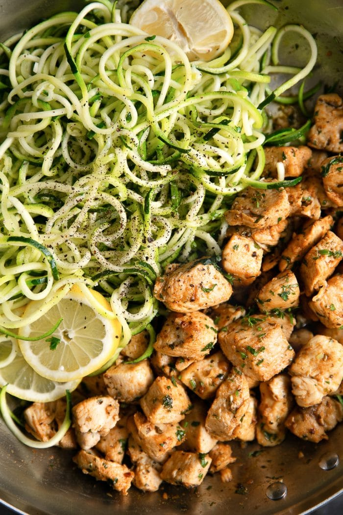 Overhead image of cooked chicken pieces cooked in butter and garlic and served with zucchini noodles with lemon.