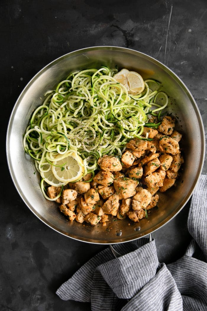 Over head image showing a large skillet filled with zucchini noodles on one half of the skillet and garlic butter chicken pieces of the other half of the skillet.