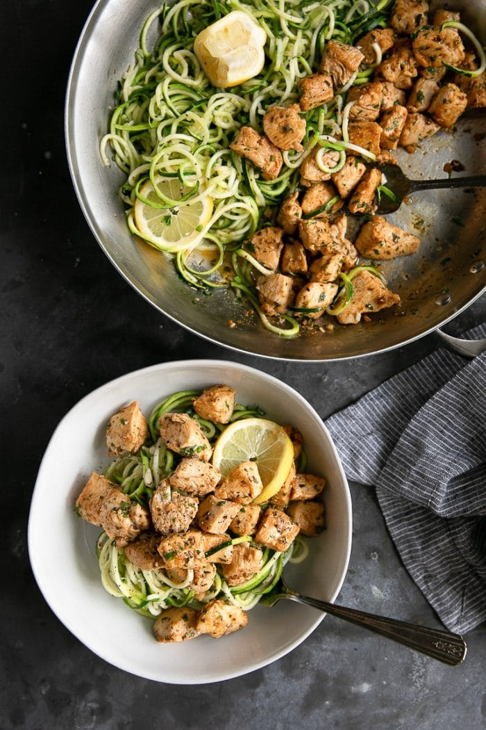 Skillet and white bowl filled with zucchini noodles and garlic butter chicken bites.