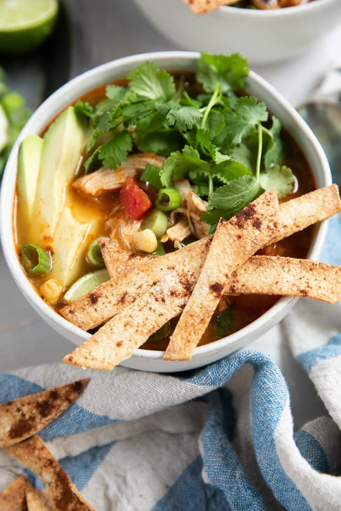 White bowls filled with chicken enchilada soup and garnished with homemade baked tortilla strips, cilantro, and avocado.