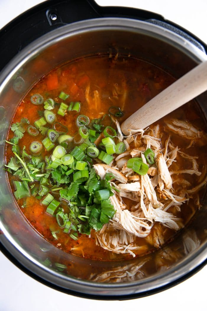 Shredded chicken, cilantro, and green onions added to the bowl of the Instant pot.