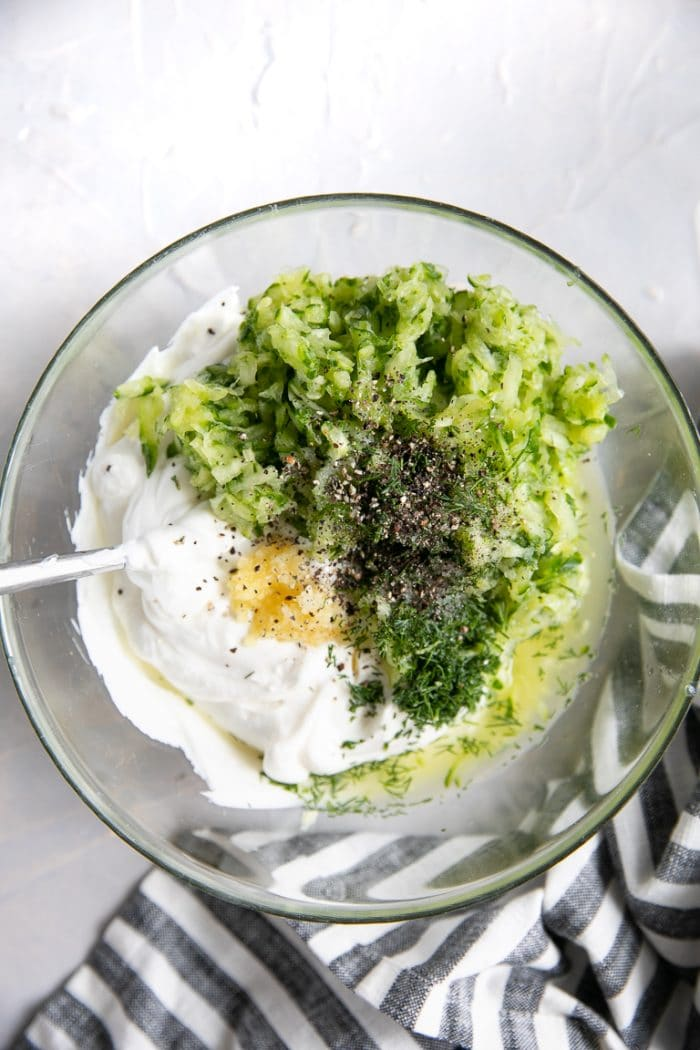 Glass bowl filled with plain Greek yogurt, lemon juice, cucumber, garlic, fresh dill, salt, and pepper.