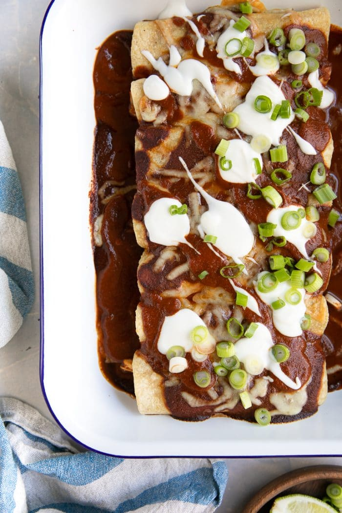 Fully cooked baking dish filled with chicken enchiladas topped with enchilada sauce and garnished with cheese, sour cream, and green onions.