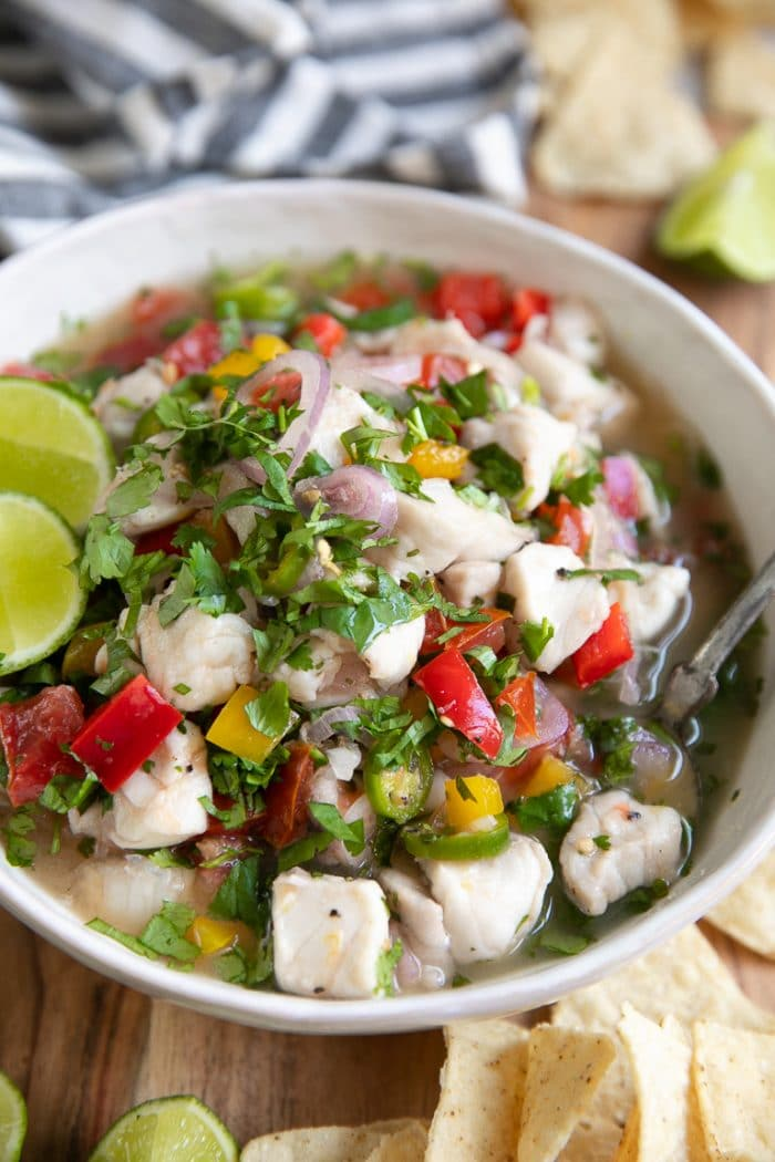Large white shallow bowl filled with fish ceviche and garnished with fresh cilantro.