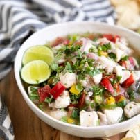 WHite shallow bowl filled with fish ceviche.