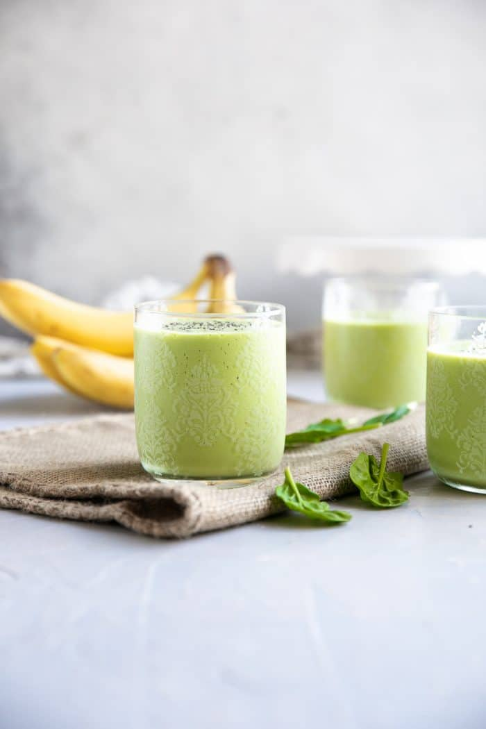 Three glasses filled with green smoothie made with yogurt, milk, spinach, mango, peach, and chia seeds.
