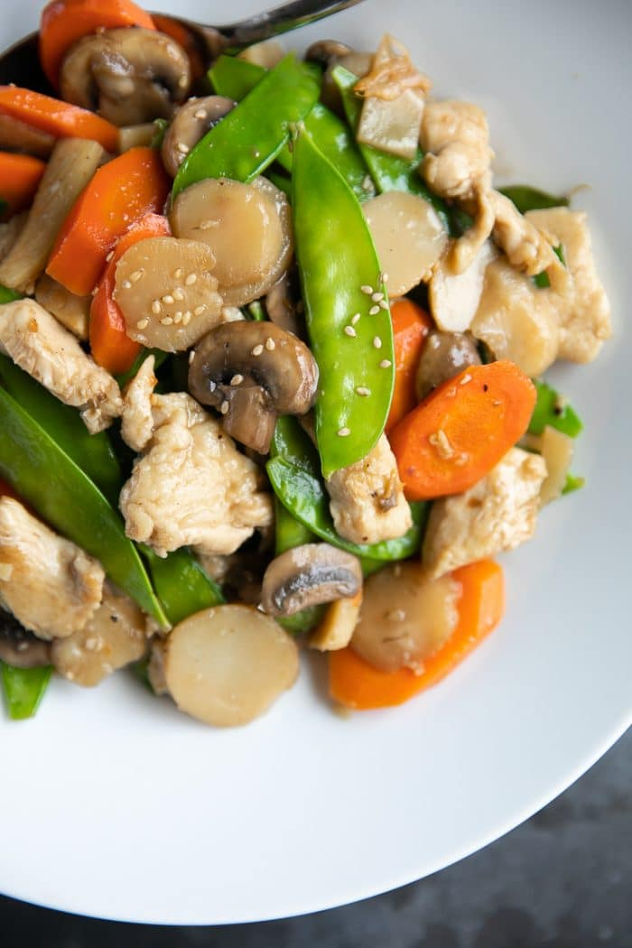 Moo Goo Gai Pan made with snow peas, water chestnuts, carrots, chicken, mushrooms, in a light sauce in a white shallow bowl.