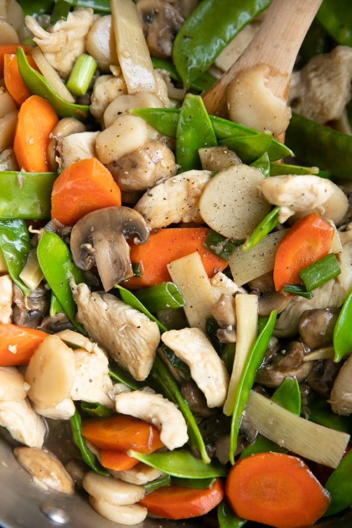 Large pan filled with stir-fried chicken, mushrooms, snow peas, carrots, water chestnuts, green onion, and chicken.