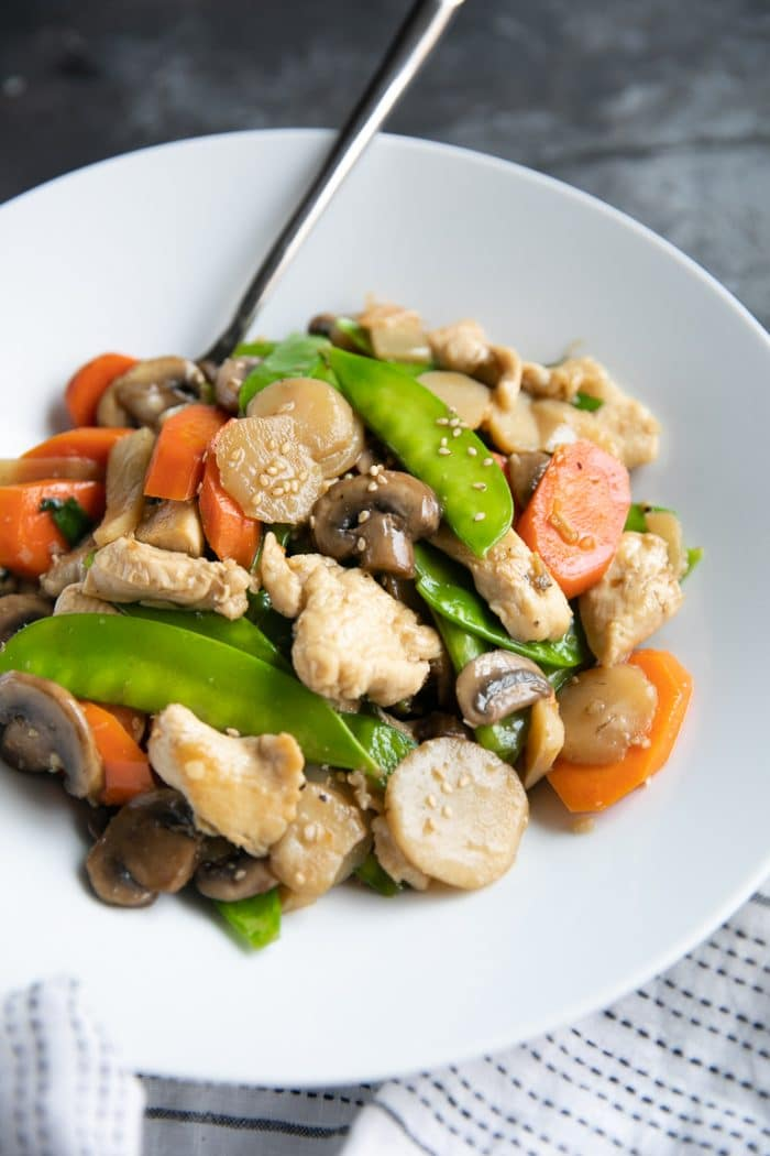 Large white shallow bowl filled with Moo Goo Gai Pan made with chicken, sliced carrots, mushrooms, and snow peas.