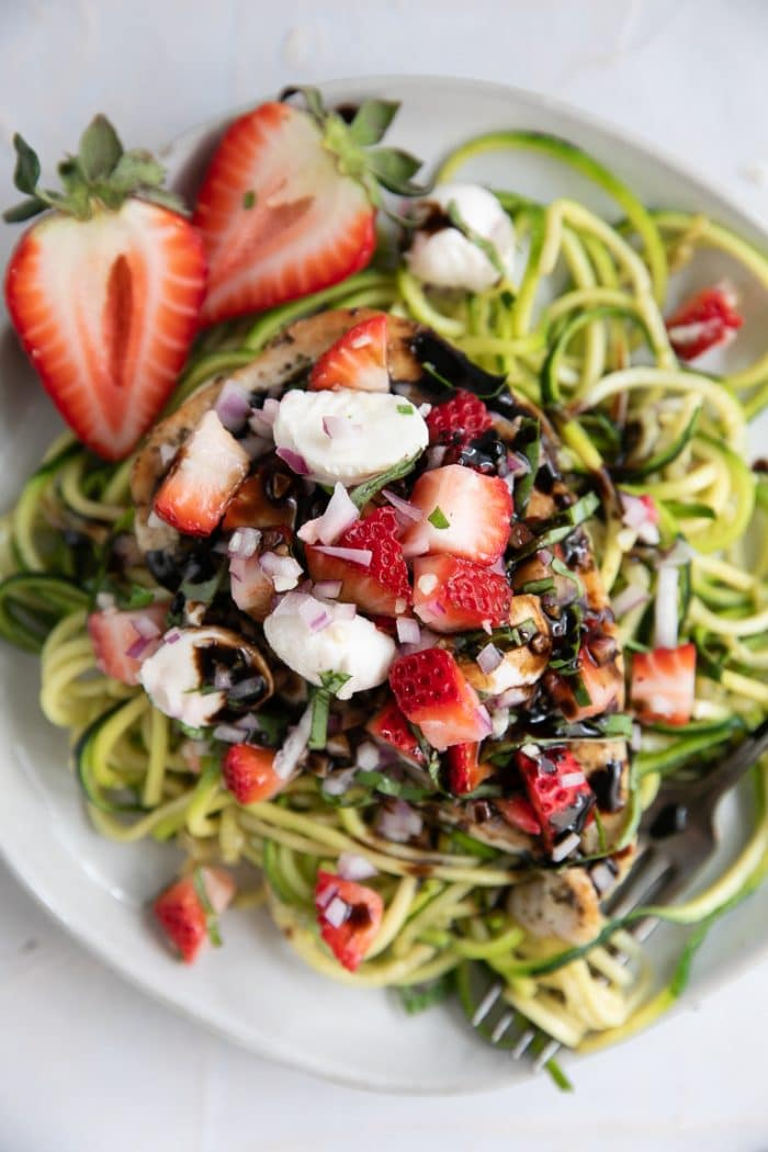 A bowl of strawberry bruschetta chicken on a plate, with zoodles