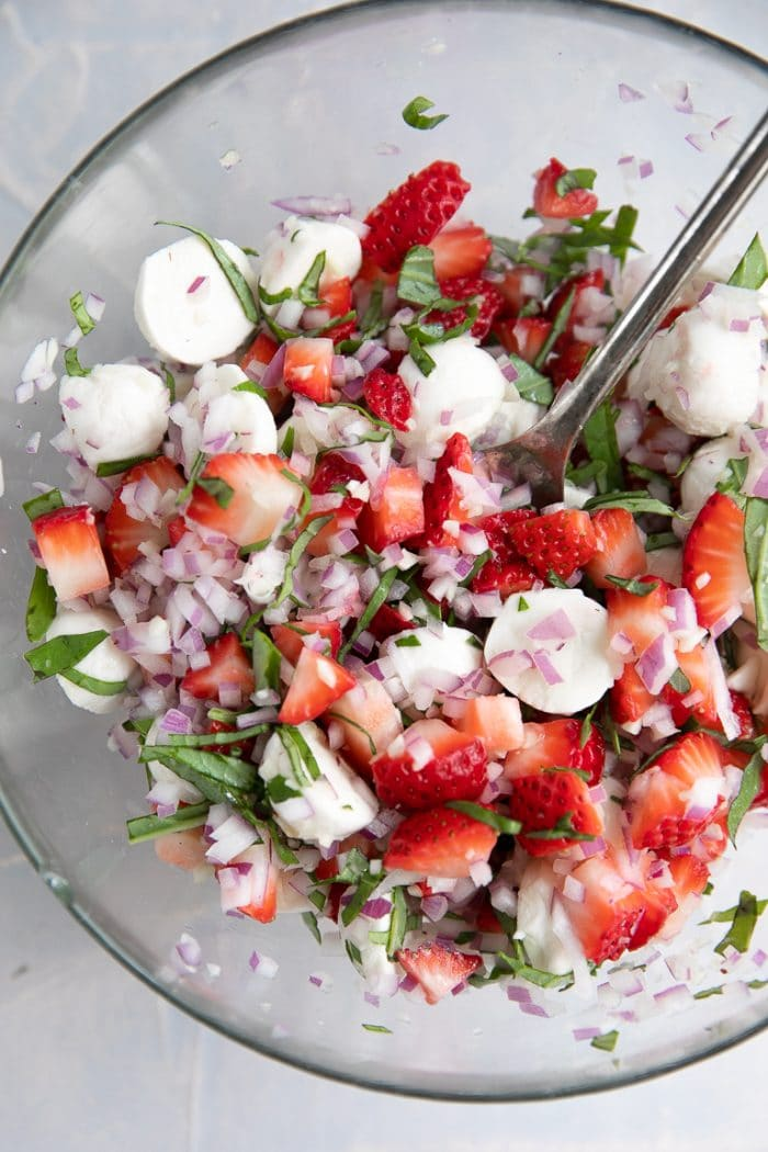 A bowl of salad on a plate, with strawberries and Bruschetta