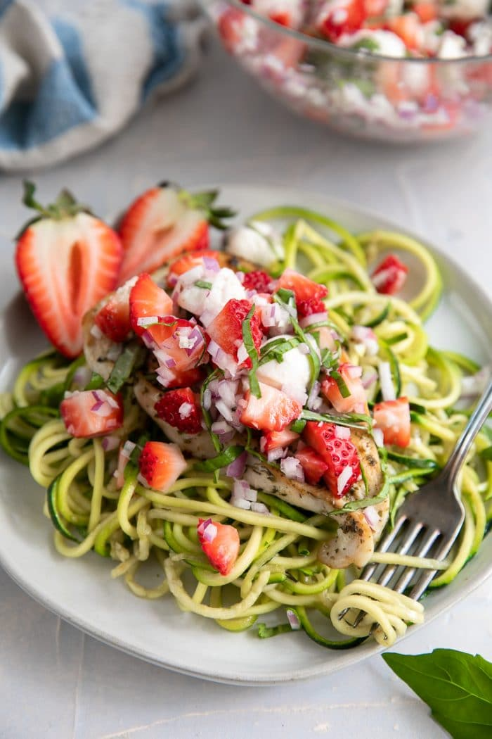 A bowl of zoodles on a plate, with Strawberry bruschetta chicken