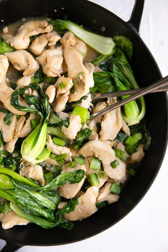 Skillet filled with stir fried chicken, baby bok choy, and green onions