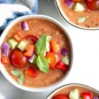 Bowls of gazpacho topped with diced cucumber, tomato, red onion, and bell pepper.