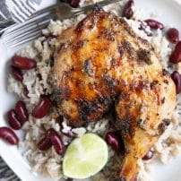 Overhead image of grilled jerk chicken on a white plate with Jamaican rice and peas.