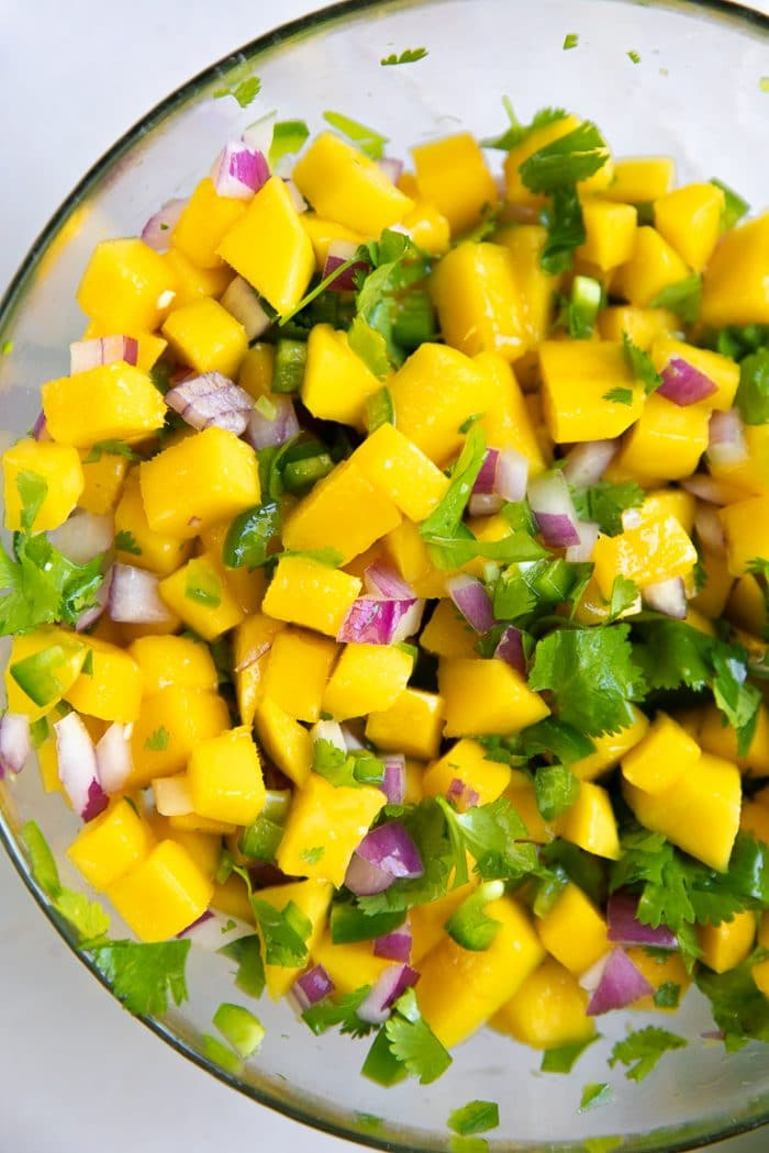 Glass mixing bowl filled with mixed together mango salsa.