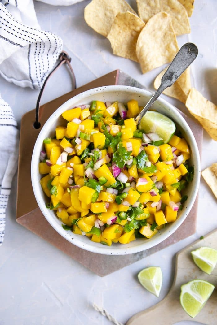 Mango salsa with tortilla chips and garnished with fresh lime wedges.