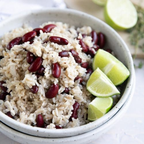 Stacked bowls with the top bowl filled with Jamaican Rice and Peas and garnished with fresh lime wedges.