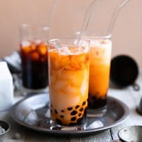 Three glasses filled with thai tea boba.