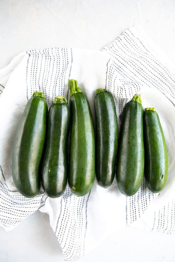 Six whole raw zucchini.
